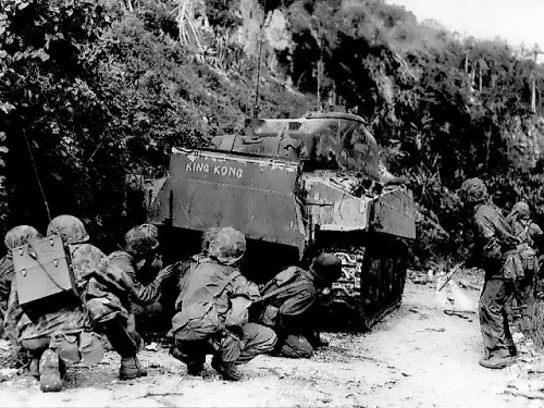Marines take cover behind a M4 Sherman tank while clearing out the northern end of Saipan, 8 July 1944.