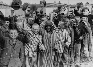 Prisoners wave at troops at the liberation of Dachau, 1945